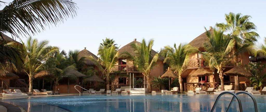 Piscine extérieure, palmiers et chaises longues, transats à l'hôtel Lamantin 5* à Saly, au Sénégal